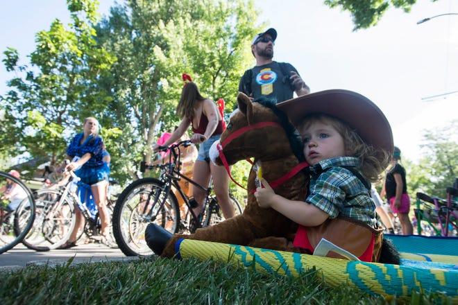 Jack Bristow, 1, sits back and watches parade participants bike by during the Tour de Fat Bike parade on Saturday, Sept. 1, 2018, in Fort Collins, Colo.