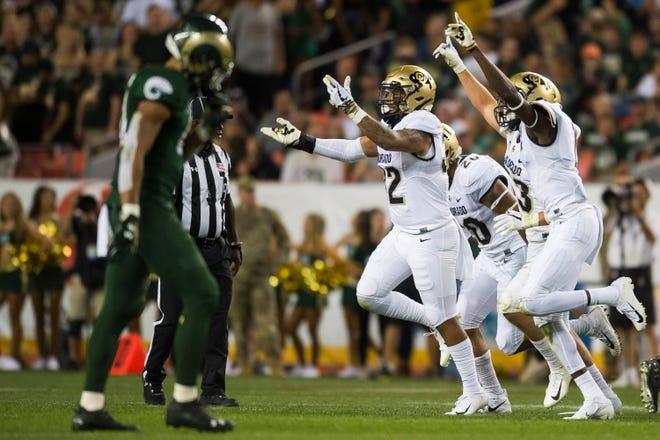 University of Colorado defenders celebrate after an interception of Colorado State University senior quarterback K.J. Carta-Samuels (1) on Friday, Aug. 31, 2018, at Broncos Stadium in Denver, Colo.