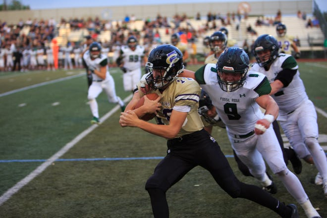 Fort Collins junior quarterback Hayden Iverson attempts to run the ball against Fossil Ridge defenders during the first half of Friday's game against Fossil Ridge.