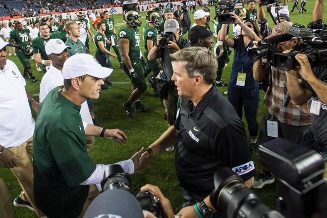Colorado State University head coach Mike Bobo, left, greets University of Colorado head coach Mike MacIntyre after a win for CU in the Rocky Mountain Showdown on Friday, Aug. 31, 2018, at Broncos Stadium in Denver, Colo.