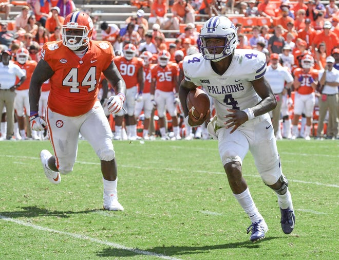 Furman quarterback Darren Grainger (4) runs from Clemson tight end Garrett Williams (44) during the fourth quarter in Memorial Stadium in Clemson on September 1.