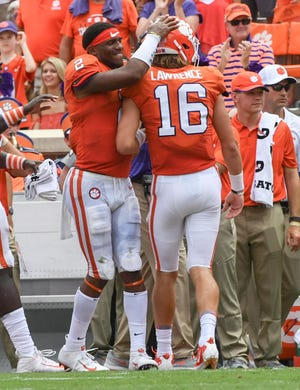 Clemson quarterback Trevor Lawrence (16) is congratulated by quarterback Kelly Bryant (2) after throwing his first career touchdown to Clemson wide receiver Diondre Overton (14) against Furman during the second quarter in Memorial Stadium in Clemson on September 1.