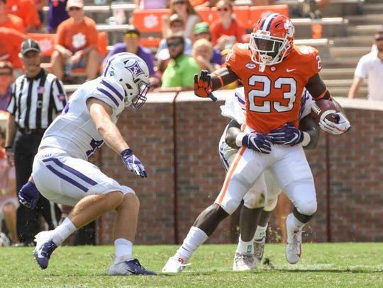 Clemson running back Lyn-J Dixon (23) runs by Furman cornerback Braedon Domino (16) during the third quarter in Memorial Stadium in Clemson on September 1.