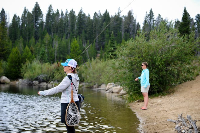 Shalon Hastings, a founding member of Last Chance Fly Gals gives some helpful casting tips to Jennifer Davis, right, on a recent fishing trip up to Park Lake in Helena, Mont., with some women from the fishing group.  (Thom Bridge/Independent Record via AP)