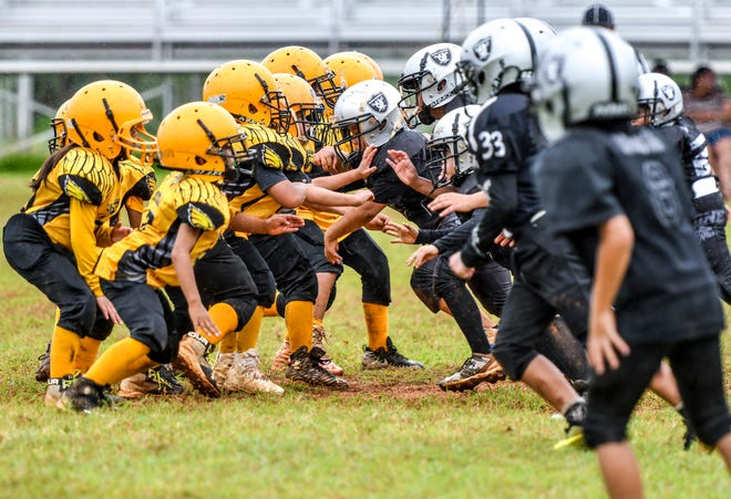 The Guam Raiders and Granite Eagles battled for muddy yardage during their Guam National Youth Football Federation matchup in Tiyan in Saturday, Sept. 1, 2018. In the hotly contested game, the Eagles soared away with the victory over the Raiders, final score 20-12.