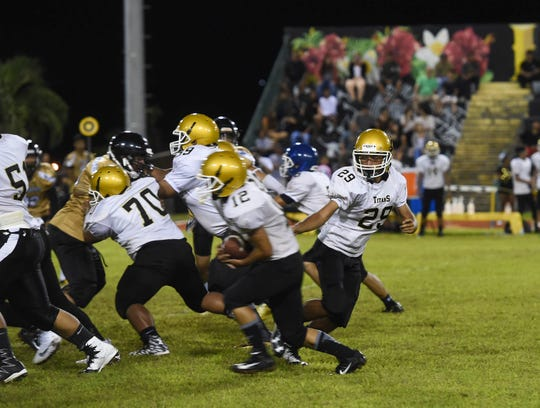 Tiyan High quarterback John Angoco (29) hands the ball off to running back Vincent Gamallo (12) during an Independent Interscholastic Athletic Association of Guam High School Football League game at Ramsey Field on Sept. 1, 2018.