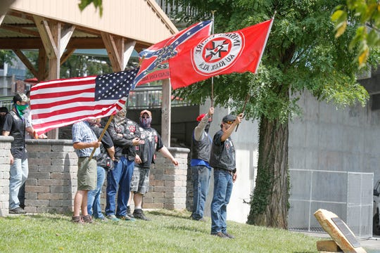 "Members of the Klan wave flags and taunt counter-protesters during the Ku Klux Kookout last year in Anderson, Ind. This year's ""kookout"" takes place Saturday."