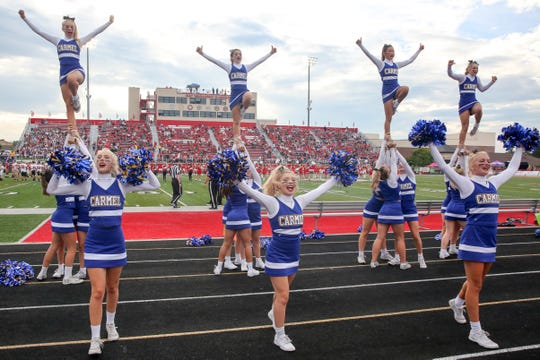 The Carmel cheerleaders lead the crowd in some cheers during the first half of Center Grove vs. Carmel High School varsity football held at Center Grove High School, August 31, 2018.