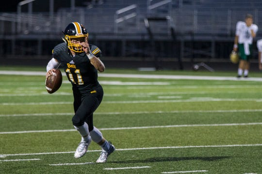 Bettendorf quarterback Carter Bell rolls out of the pocket during a 4A varsity football game on Friday, Aug. 31, 2018, at TouVelle Stadium in Bettendorf.