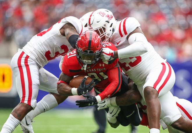 Sep 1, 2018; Houston, TX, USA; Texas Tech Red Raiders running back Da'Leon Ward (21) runs with the ball as Mississippi Rebels defensive back Zedrick Woods (36) and linebacker Detric Bing-Dukes (43) attempt to make a tackle during the second quarter at NRG Stadium. Mandatory Credit: Troy Taormina-USA TODAY Sports
