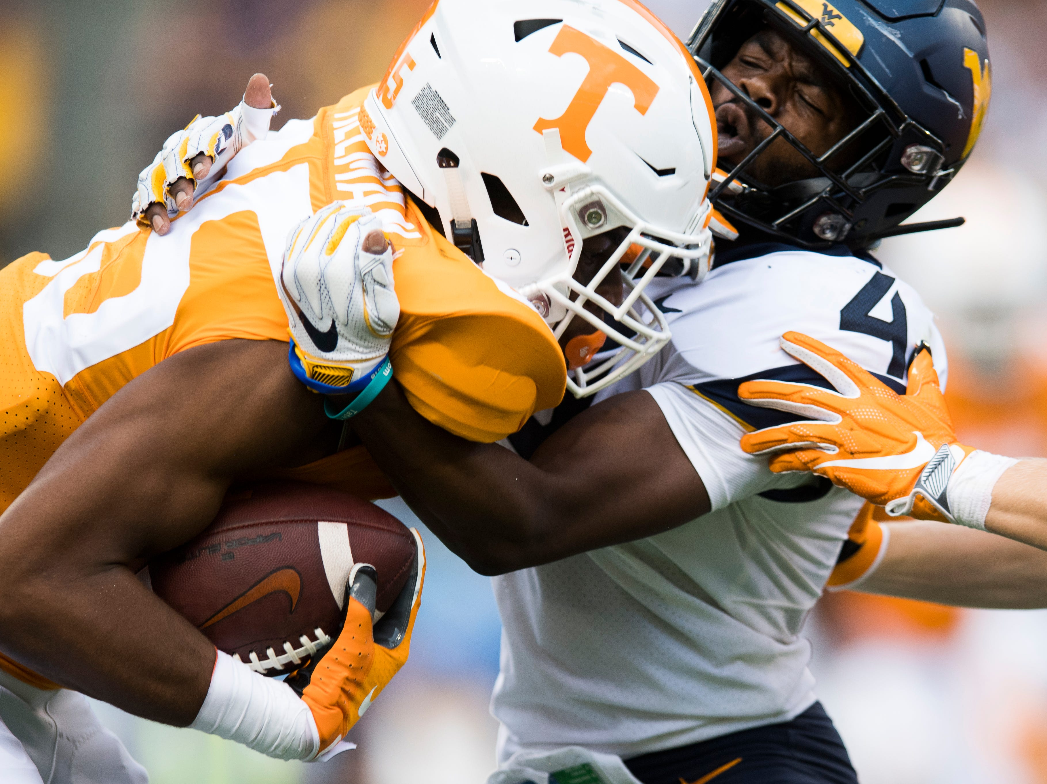 West Virginia safety Josh Norwood (4) defends against Tennessee wide receiver Cedric Tillman (85) during the Belk College Kickoff between Tennessee and West Virginia at Bank of America Stadium in Charlotte, North Carolina on Saturday, September 1, 2018.