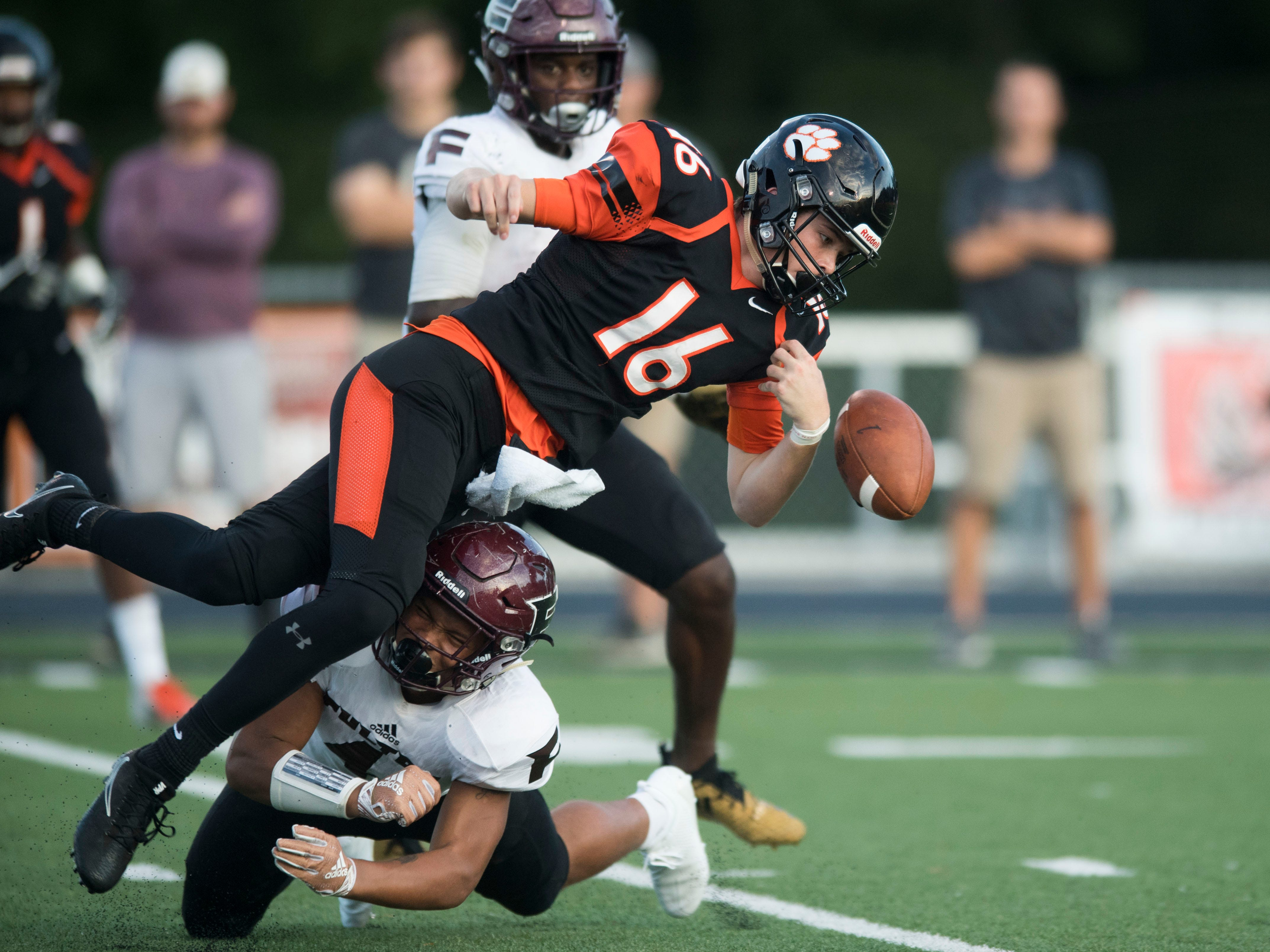 Fulton's Robquan Thomas' (4) hit caused Powell's Walker Trusley (16) to fumble the ball during the football game at Powell on Friday, August 31, 2018.
