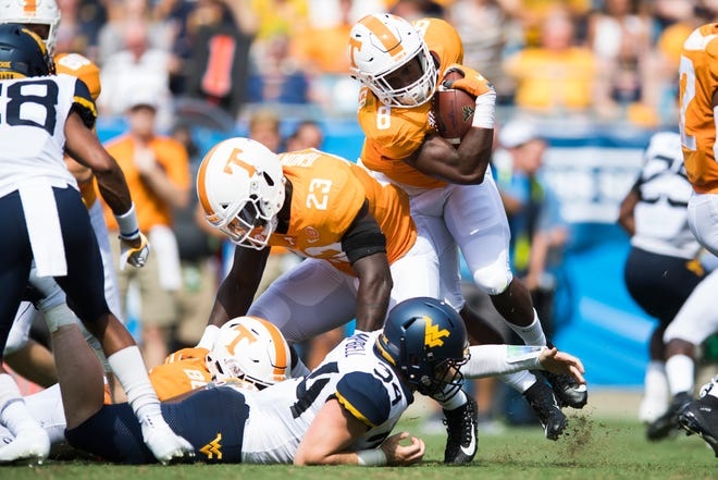 Tennessee running back Ty Chandler tries to get around Tennessee linebacker Will Ignont (23) during the Belk College Kickoff between Tennessee and West Virginia at Bank of America Stadium in Charlotte, North Carolina on Saturday, September 1, 2018.