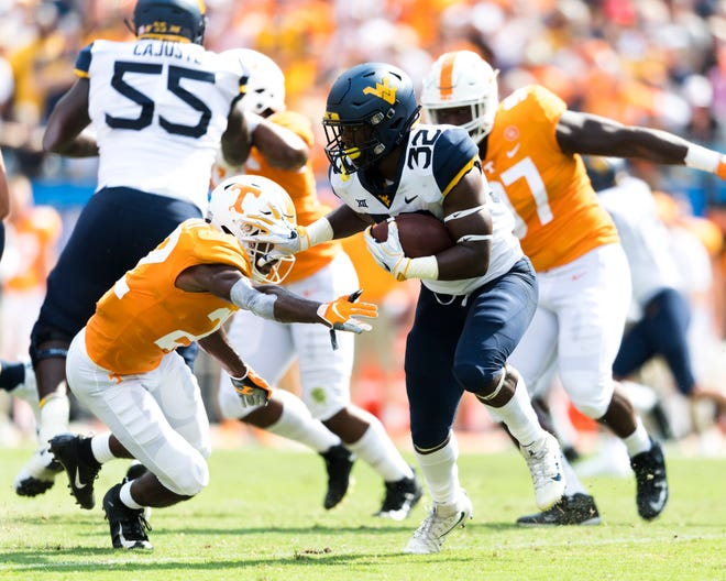 West Virginia running back Martell Pettaway (32) pushes away Tennessee defensive back Micah Abernathy (22) during the Belk College Kickoff between Tennessee and West Virginia at Bank of America Stadium in Charlotte, North Carolina on Saturday, September 1, 2018.