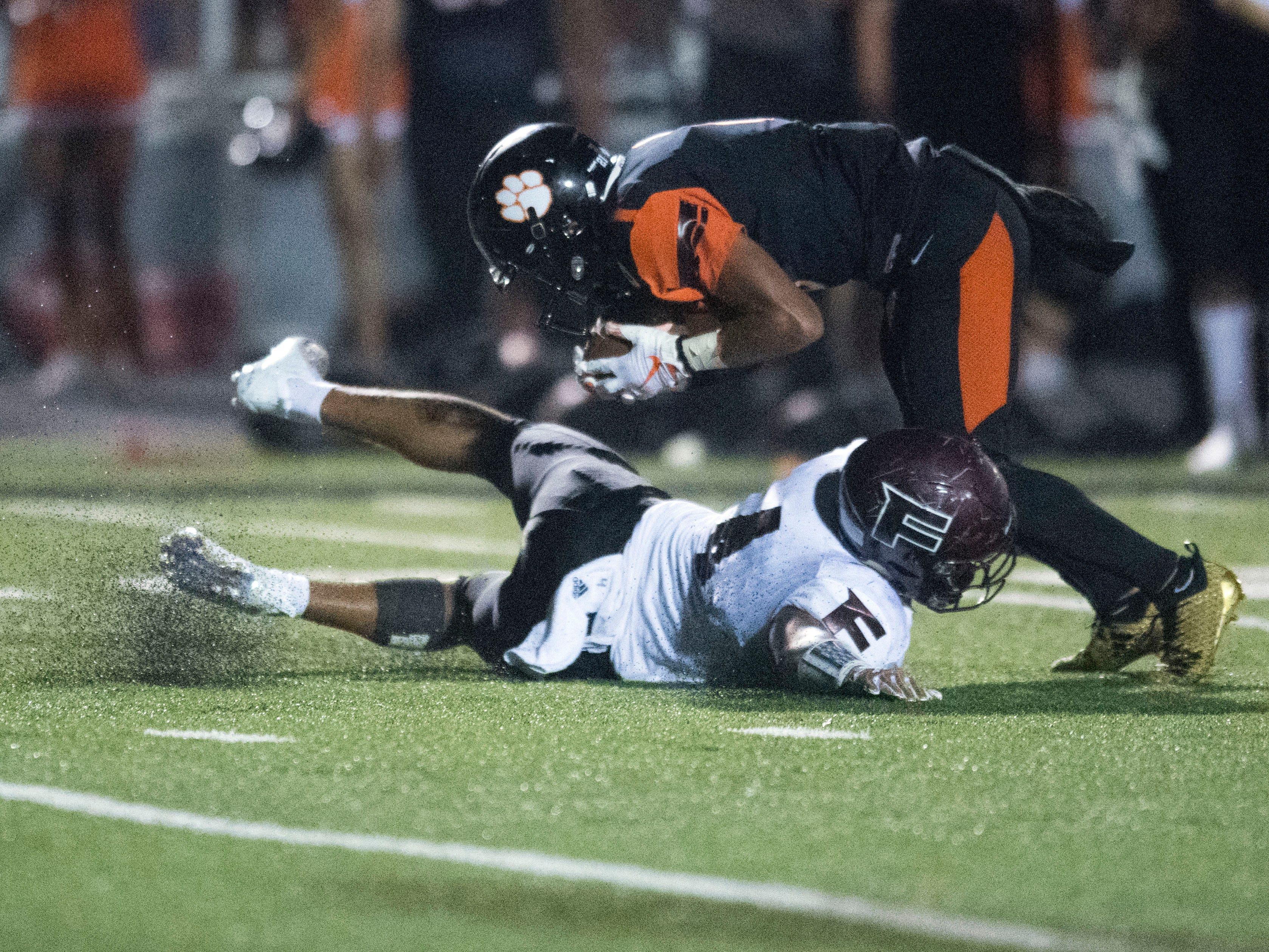 Powell's Riley Bryant (6) is hit by Fulton's Robquan Thomas (4) during the football game at Powell on Friday, August 31, 2018.