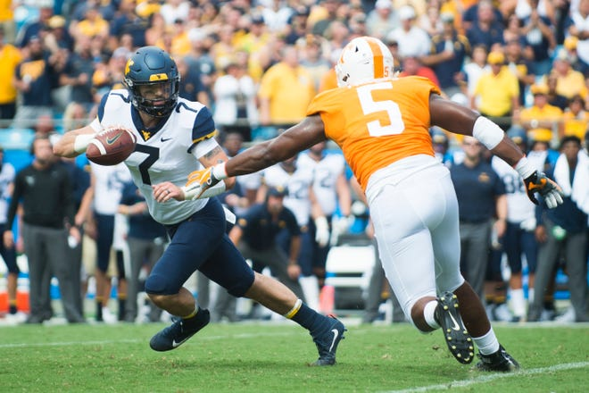 West Virginia quarterback Will Grier (7) looks to throw past Tennessee defensive lineman Kyle Phillips (5) during the Belk College Kickoff between Tennessee and West Virginia at Bank of America Stadium in Charlotte, North Carolina on Saturday, September 1, 2018.