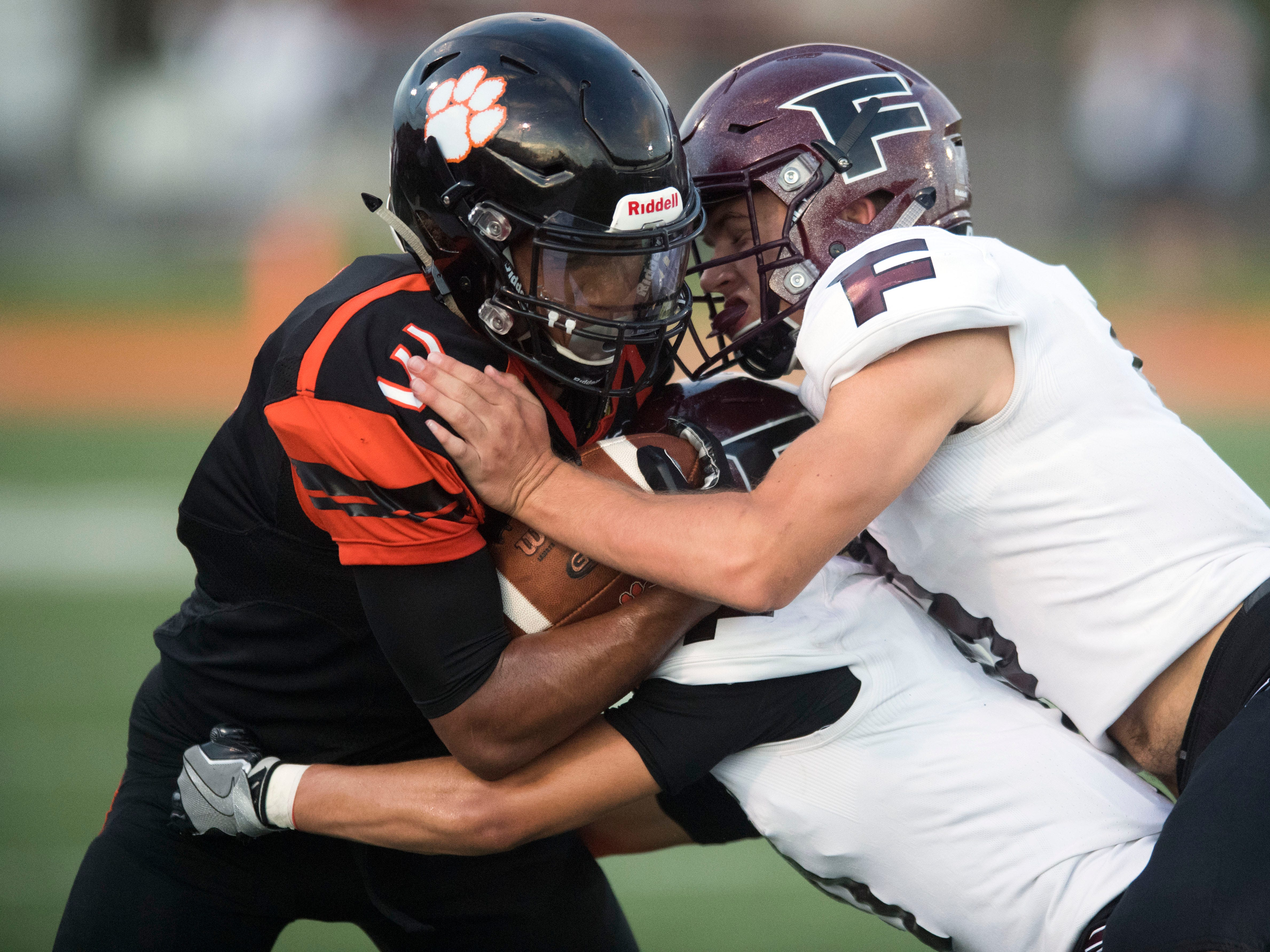 Powell's Bailor Walker (3) is hit by Fulton's Kenny Buley (11) and Tommy Sweat (9) during the football game at Powell on Friday, August 31, 2018.