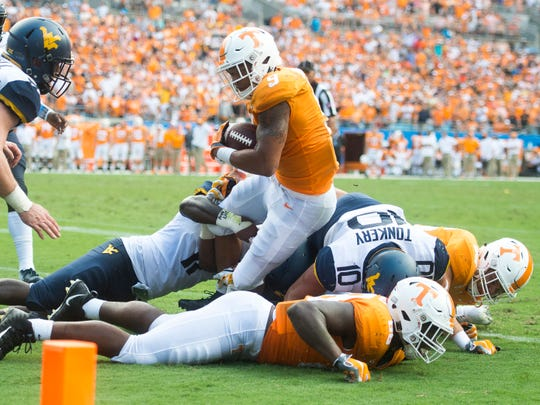 Tennessee running back Tim Jordan (9) fights for extra yards during the Tennessee Volunteers' game against West Virginia in the Belk College Kickoff at Bank of America Stadium in Charlotte, N.C., on Saturday, Sept. 1, 2018.