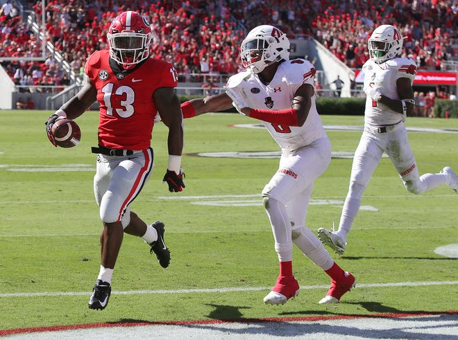 Georgia running back Elijah Holyfield gets in the endzone past Austin Peay defender Isaiah Norman during the first half of an NCAA college football game, Saturday, Sept. 1, 2018, in Athens, Ga.