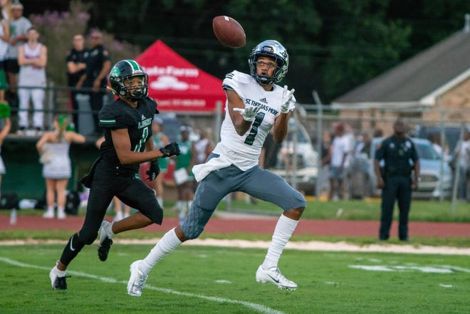 STM's Deion Senegal attempts to catch a pass as the Lafayette High School Mighty Lions take on the St. Thomas More Cougars at LHS on Aug. 31, 2018.