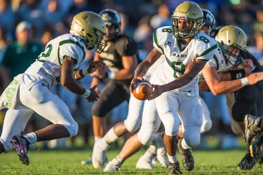 Acadiana quarterback Keontae Williams hands off to Rams' halfback Larryll Greene during their 27-20 win over Kaplan on Friday.