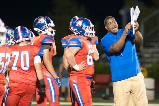 Jason Hilliard, the CAL offensive football coach, shows team members a play during warm-up just before the start of the game against Central Hardin.August 31, 2018