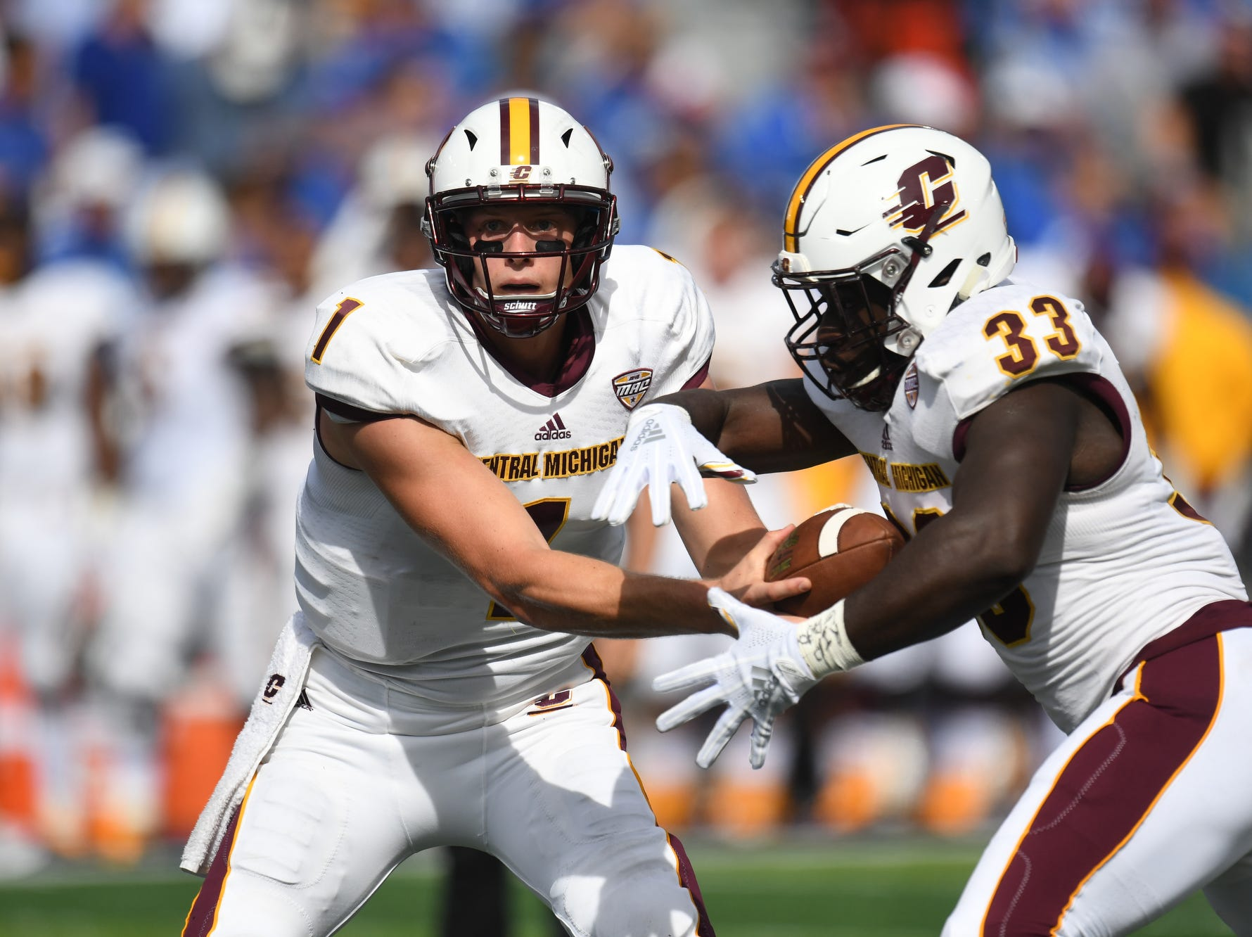 Central Michigan QB Tony Polijan hands off the ball to RB Kumehnnu Gwilly during the University of Kentucky football game against Central Michigan at Kroger Field in Lexington, Kentucky on Saturday, September 1, 2018.