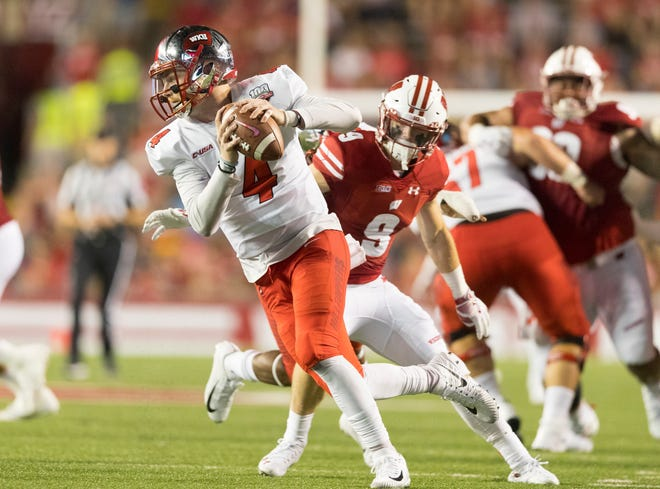 Western Kentucky Hilltoppers quarterback Drew Eckels (4) spins away from pressure applied by Wisconsin Badgers safety Scott Nelson (9) during the second quarter at Camp Randall Stadium on Friday, Aug. 31, 2018, in Madison, Wisconsin.