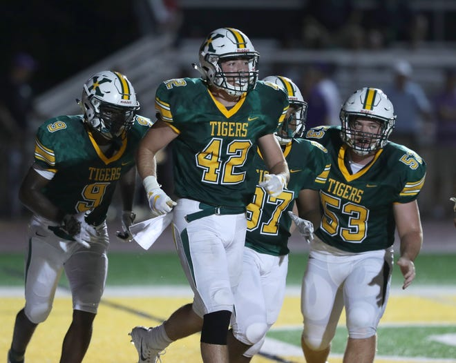 St. Xavier's Anthony Moretti, 42, leads his teammates off the field after scoring their first touchdown. Aug. 31, 2018.