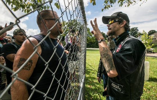 At right, Jack Noble, member of the Honorable Sacred Knights of the Ku Klux Klan, talks with a protestor through a chainlink fence barrier at the Jaycee Park in Madison, Ind. Saturday, Sept.1, 2018