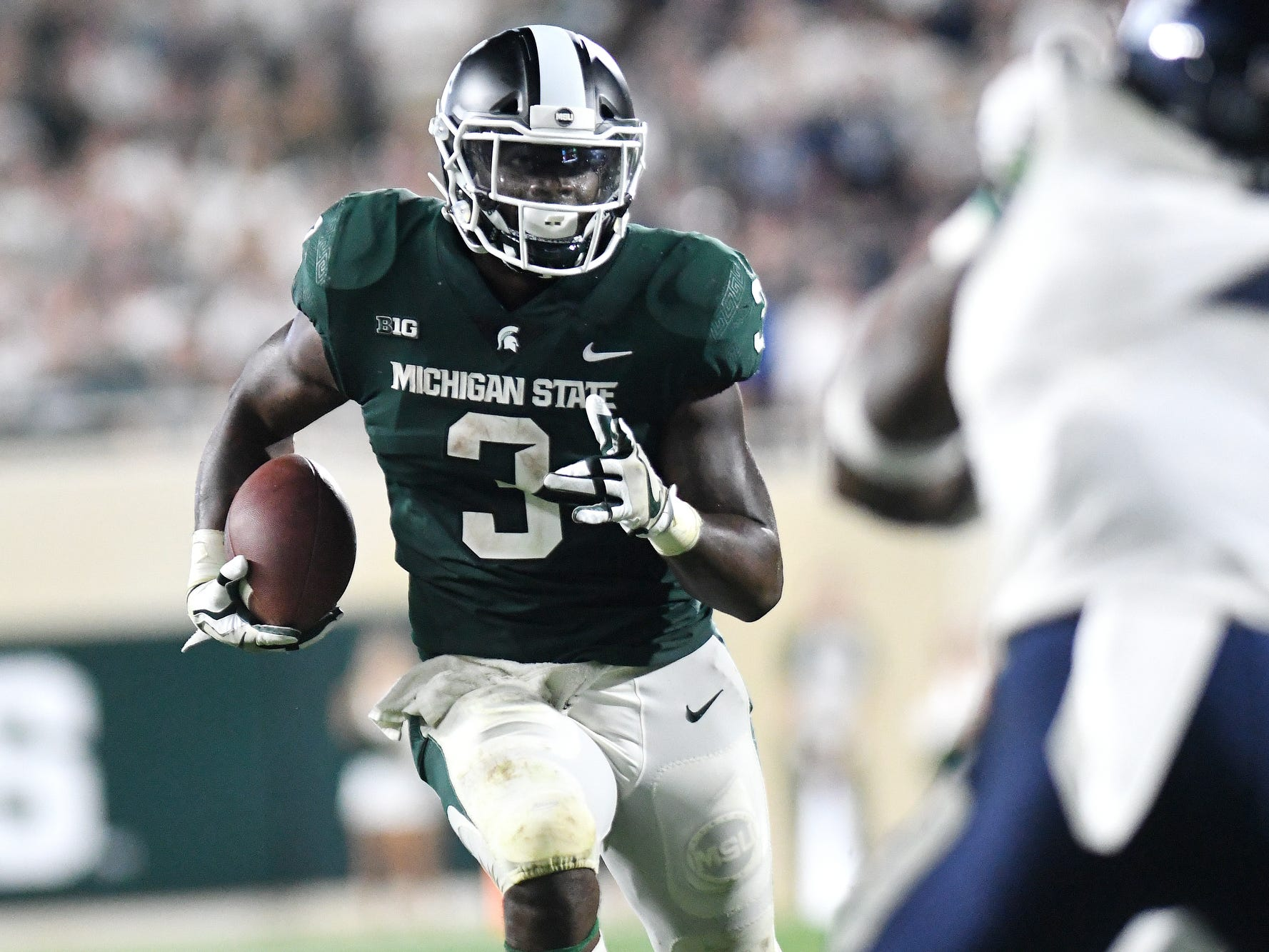 Michigan State's LJ Scott runs with the ball during the fourth quarter on Friday, Aug. 31, 2018, at Spartan Stadium in East Lansing.