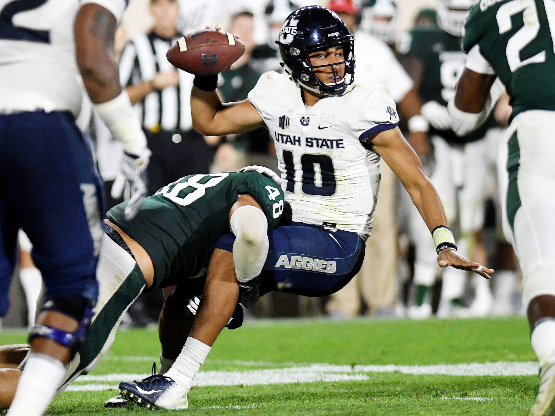 Michigan State's Kenny Willekes, left, tackles Utah State's Jordan Love during the fourth quarter on Friday, Aug. 31, 2018, at Spartan Stadium in East Lansing.