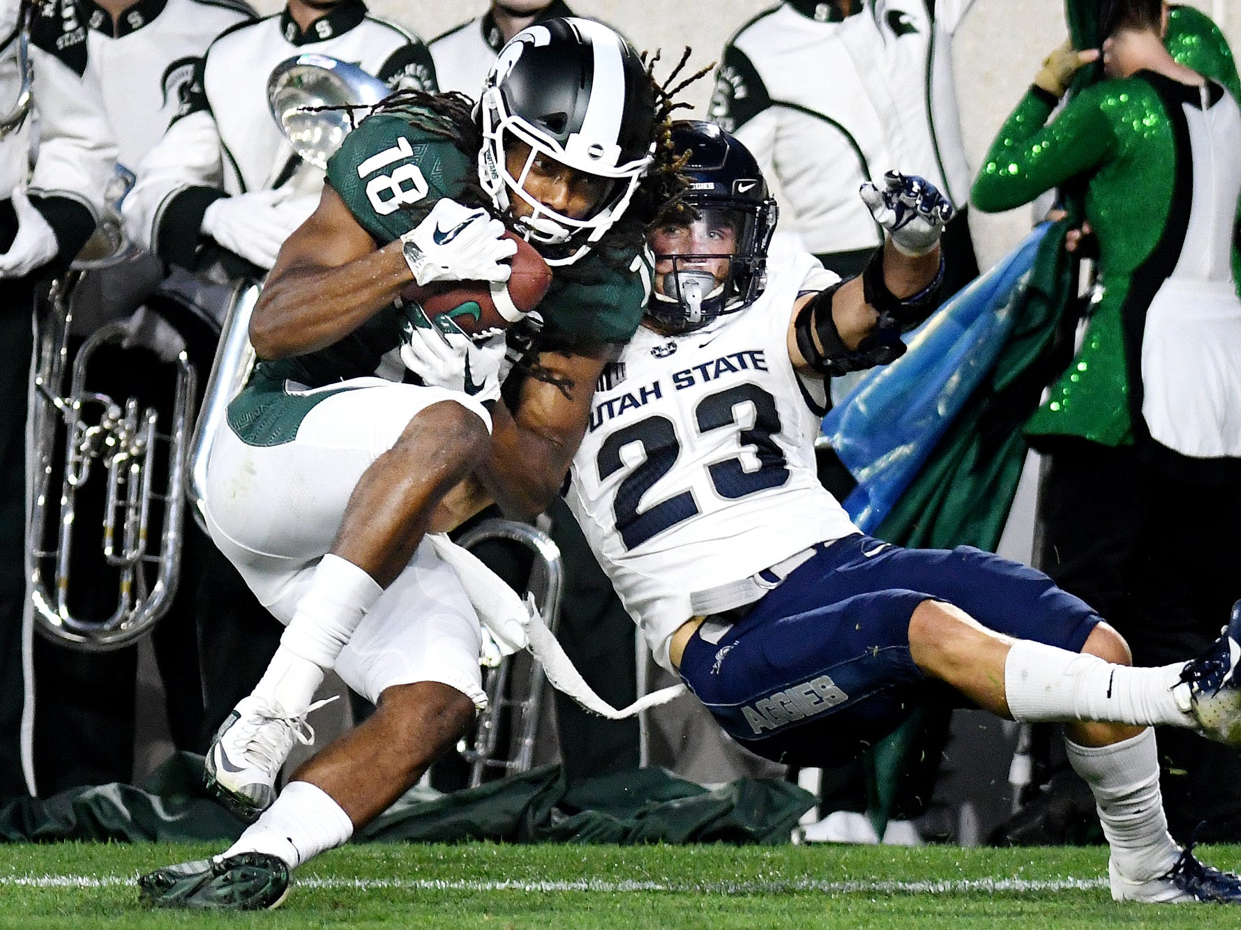 Michigan State's Felton Davis III, left, catches a touchdown as Utah State's Gaje Ferguson defends during the second quarter on Friday, Aug. 31, 2018, at Spartan Stadium in East Lansing.