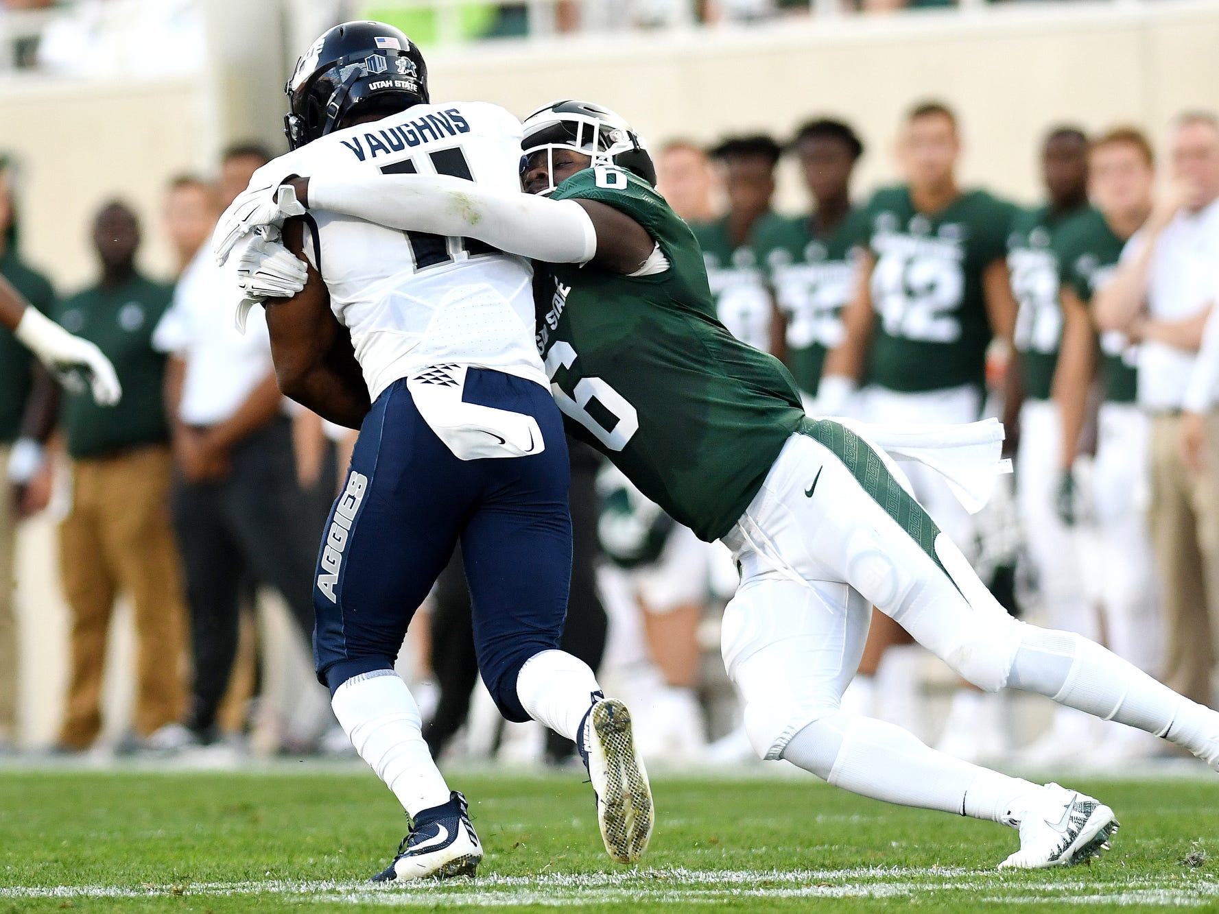 Michigan State's David Dowell, right, tackles Utah State's Aaren Vaughns during the first quarter on Friday, Aug. 31, 2018, at Spartan Stadium in East Lansing.