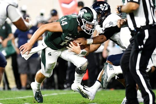 Michigan State's Brian Lewerke, left, runs for a gain as Utah State's Darwin Thompson closes in for the tackle during the second quarter on Friday, Aug. 31, 2018, at Spartan Stadium in East Lansing.