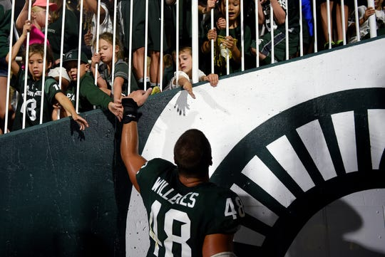 Michigan State's Kenny Willekes greets fans on his way to the locker room after the Spartans defeated Utah State on Friday, Aug. 31, 2018, at Spartan Stadium in East Lansing.