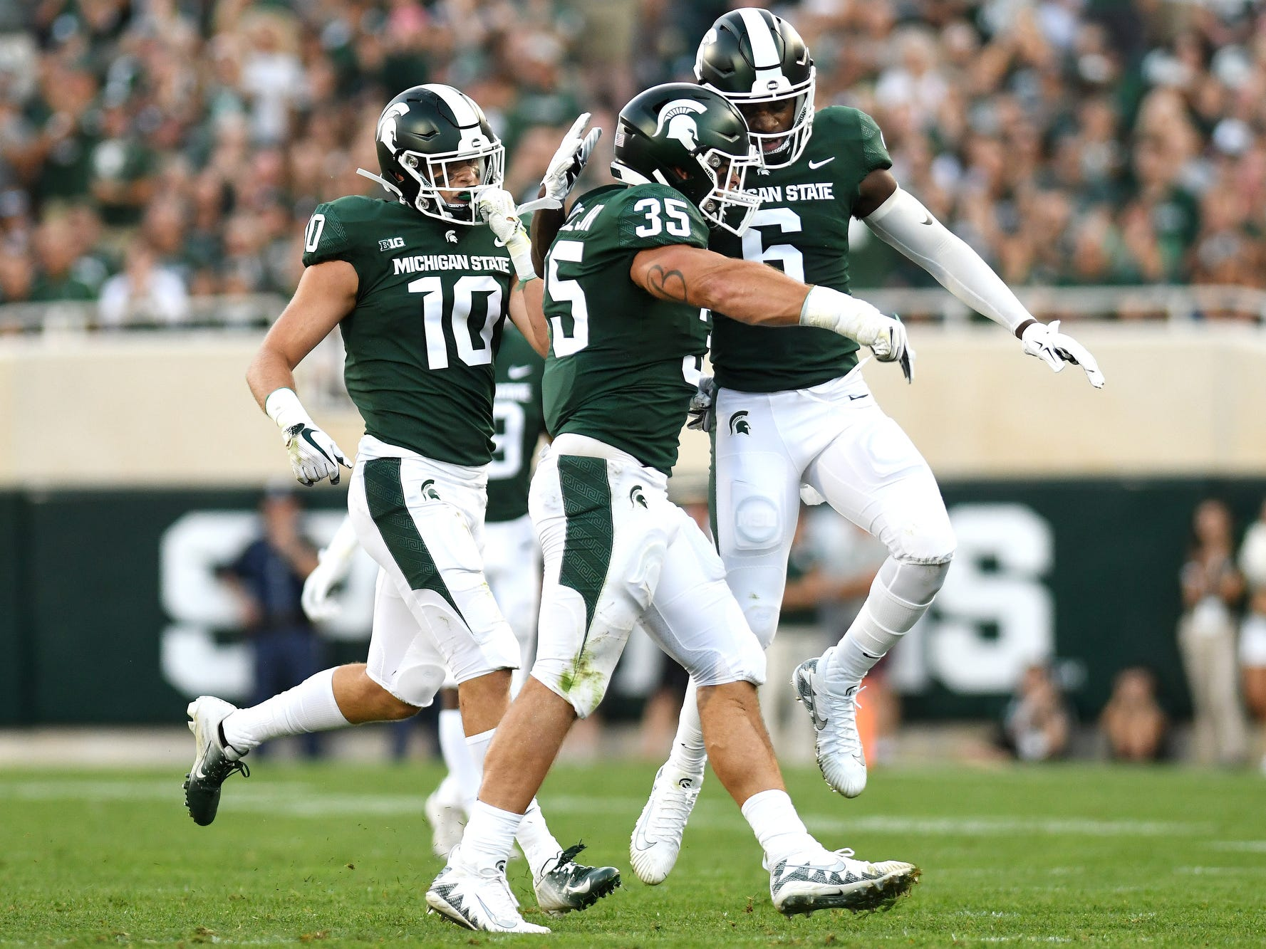 Michigan State's Joe Bachie, center, celebrates with teammates David Dowell, right, and Matt Morrissey after a stop during the first quarter on Friday, Aug. 31, 2018, at Spartan Stadium in East Lansing.