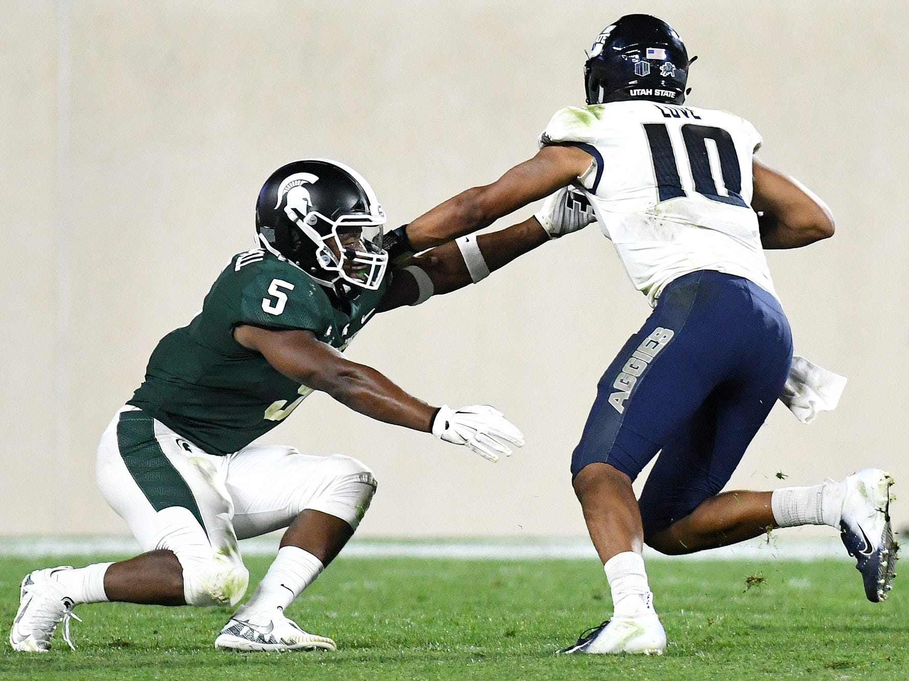 Michigan State's Andrew Dowell, left, closes in on Utah State's Jordan Love during the fourth quarter on Friday, Aug. 31, 2018, at Spartan Stadium in East Lansing.