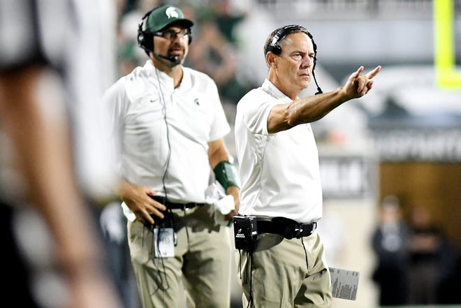 Michigan State's head coach Mark Dantonio signals to go for two points after a touchdown during the fourth quarter on Friday, Aug. 31, 2018, at Spartan Stadium in East Lansing.