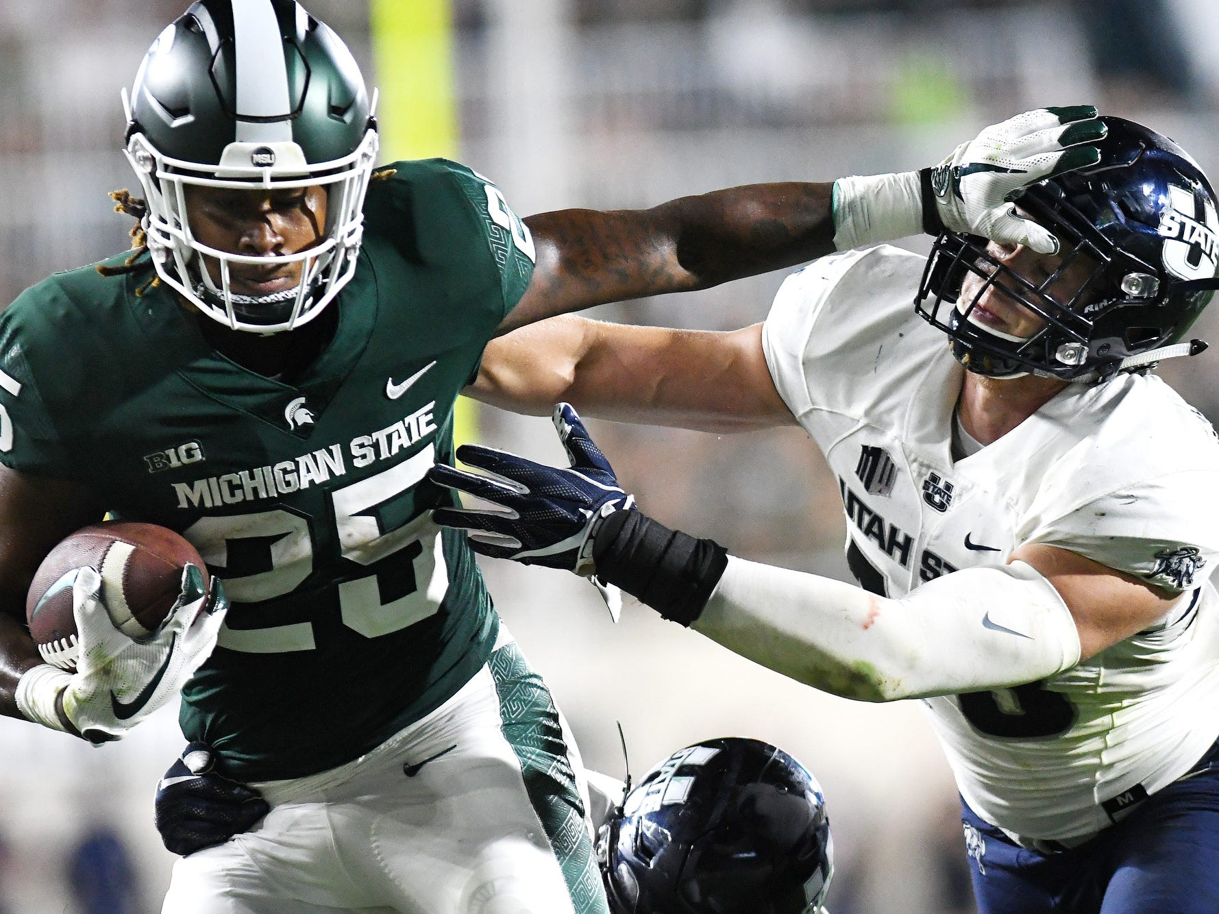 Michigan State's Darrell Stewart Jr., left, stiff arms Utah State's Chase Christiansen during the fourth quarter on Friday, Aug. 31, 2018, at Spartan Stadium in East Lansing.