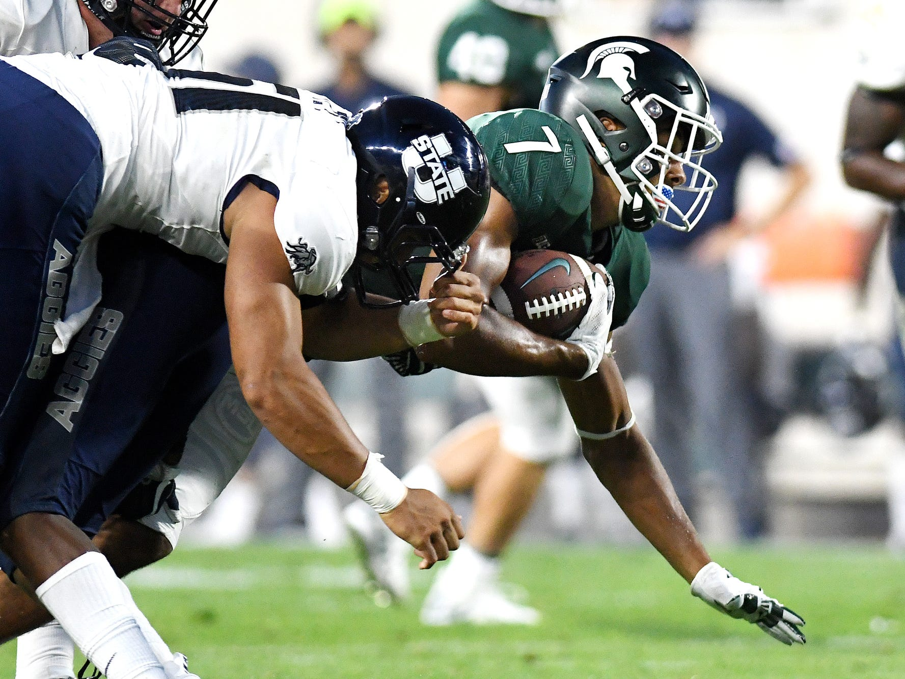 Michigan State's Cody White dives through the Utah State defense for extra yards after a catch during the second quarter on Friday, Aug. 31, 2018, at Spartan Stadium in East Lansing.