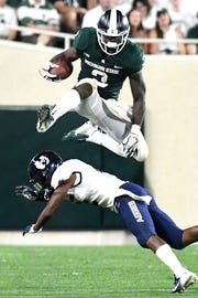 LJ Scott had a few impressive moments, including this leap over a defender, but didn't find much room to run against Utah State.