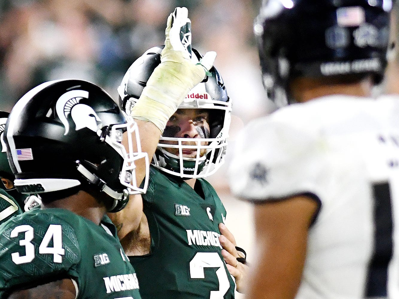 Michigan State's Joe Bachie, center, celebrates after his turnover while Utah State's quarterback Jordan Love, right, looks on during the fourth quarter on Friday, Aug. 31, 2018, at Spartan Stadium in East Lansing.