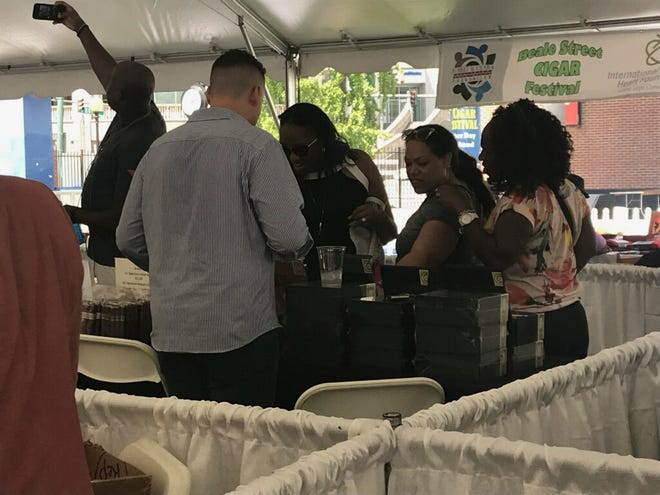 Taneta Hicks, Kristen Ellison and Sharon Hicks inspect cigars at the Beale St. Cigar Festival, held at Handy Park on Saturday.