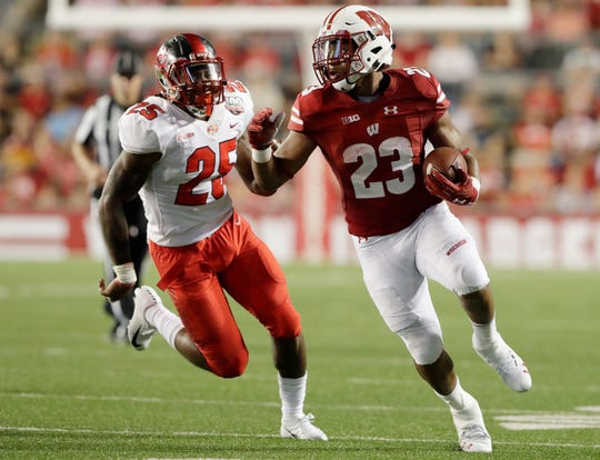Wisconsin Badgers running back Jonathan Taylor (23) scores on a 30-yard touchdown run against the Western Kentucky Hilltoppers in the second quarter of an NCAA football game at Camp Randall on Friday, August 31, 2018 in Madison, Wis.