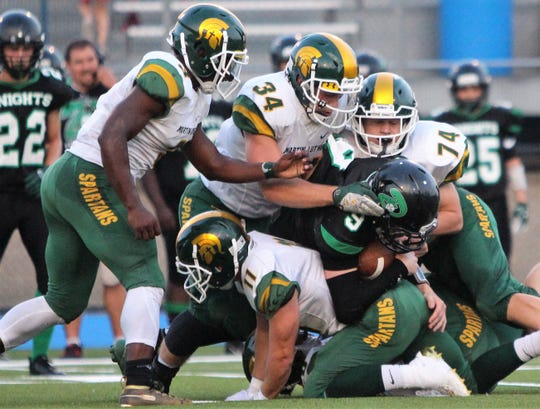 Martin Luther defenders Brody Lee (34), Michael Strohmeyer (74) and Brad Kulinski (11) combine to tackle Dominican quarterback Bo Bennett.