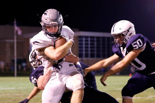 Lake Country Lutheran running back Dane Vance is brought down by three Lakeside Lutheran tacklers on August 31.