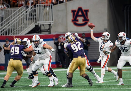 Auburn's Jarrett Stidham (8) throws the ball downfield over Washington defenders at Mercedes-Benz Stadium in Atlanta, Ga., on Saturday, Sept. 1, 2018. Auburn leads Washington 15-13 at halftime.
