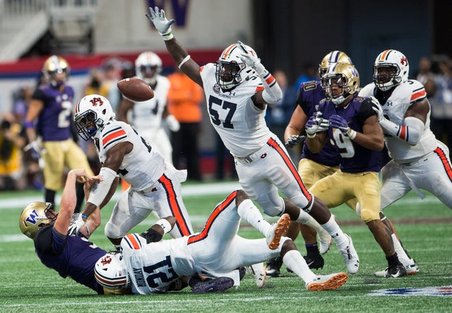 A swarm of Auburn defenders, led by safety Smoke Monday (21) and linebacker Deshaun Davis (57) bring down Washington's Jake Browning (3) as he throws a desperation pass on fourth down at Mercedes-Benz Stadium in Atlanta, Ga., on Saturday, Sept. 1, 2018. Auburn defeated Washington 21-16 in the Chick-fil-a Kickoff Game.