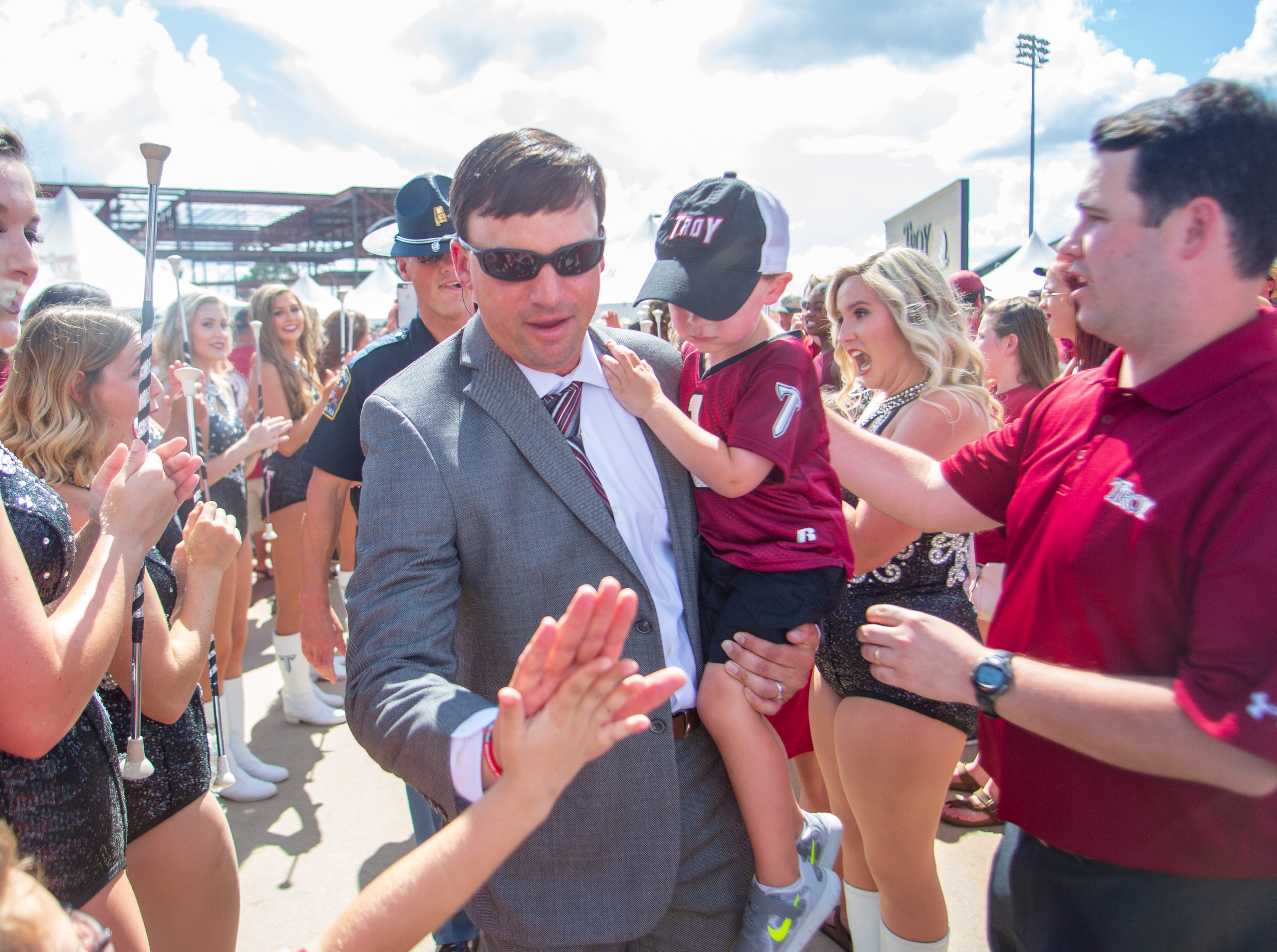 Troy's head coach Neal Brown is welcomed to the stadium and high-fives fans along the way.